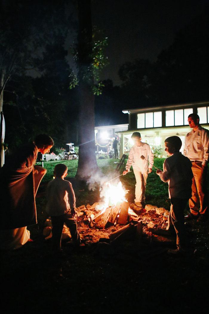 wedding guests around bonfire