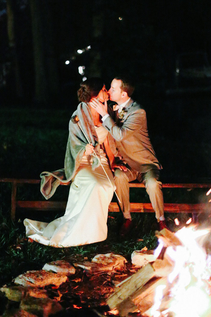bride and groom kissing by bonfire