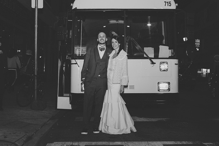 bride and groom in front of bus