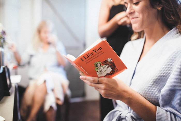 bride reading book while getting ready