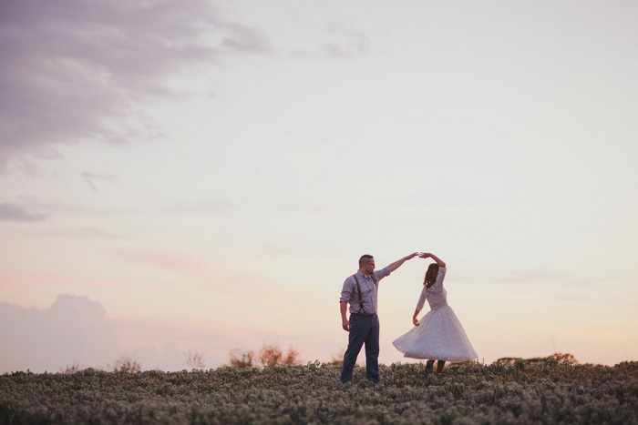 bride and groom dancing in a field