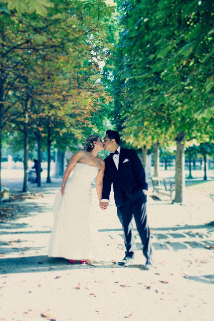bride and groom kissing on treed walkway