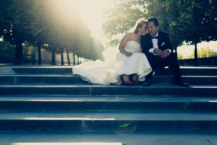 bride and groom sitting on Paris park steps
