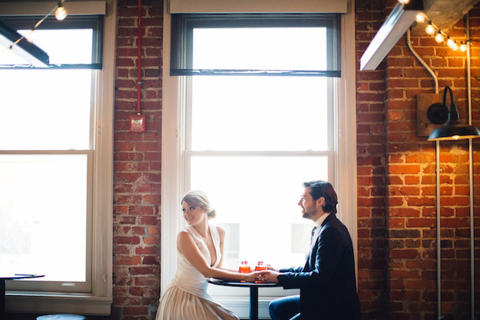 bride and groom sitting at table with cocktails
