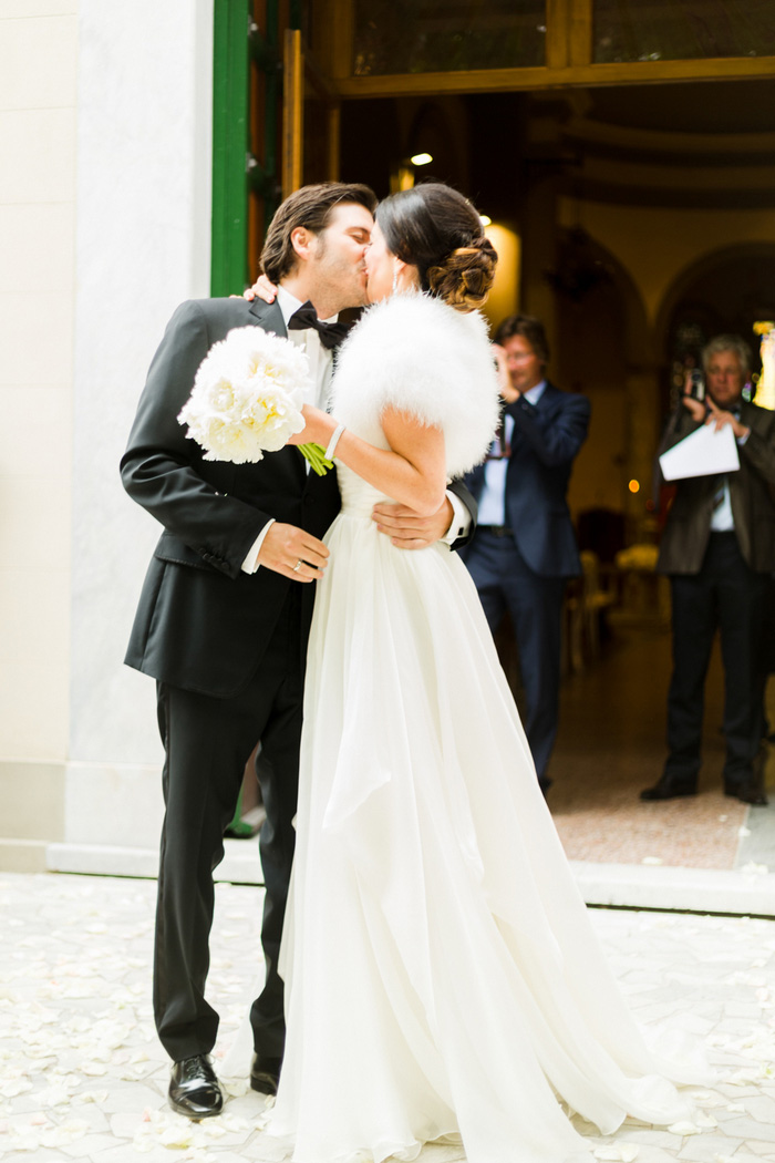 bride and groom kissing outside the church