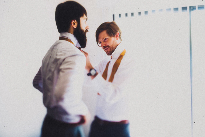 groomsman helping groom with bow tie