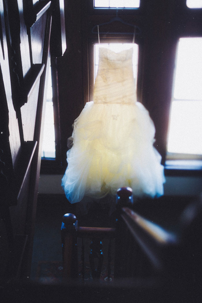 wedding dress hanging in stairwell