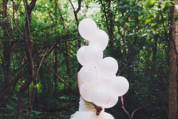 bride carrying white balloons