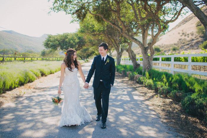 bride and groom walking down deserted road