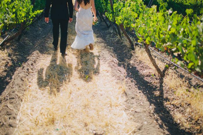bride and groom walking through vineyard
