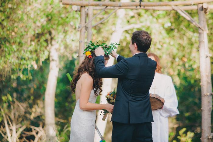 groom placing flower crown on bride's head