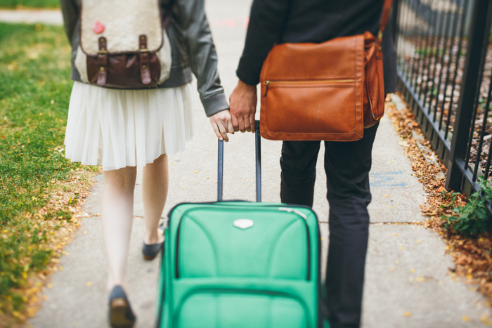 bride and groom walking with suitcase