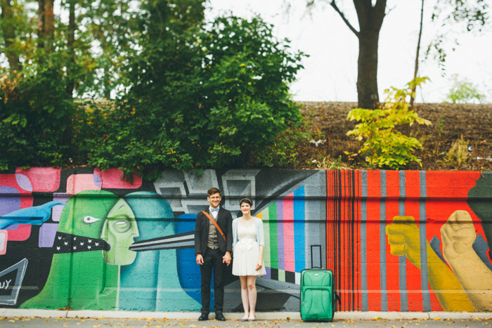 bride and groom in front of colorful mural