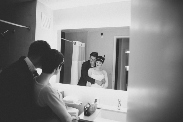 bride and groom posing in front of mirror