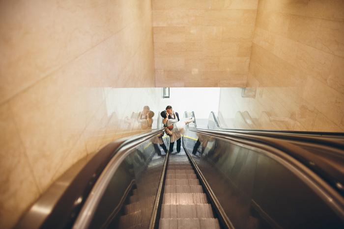 groom carrying bride on escalator