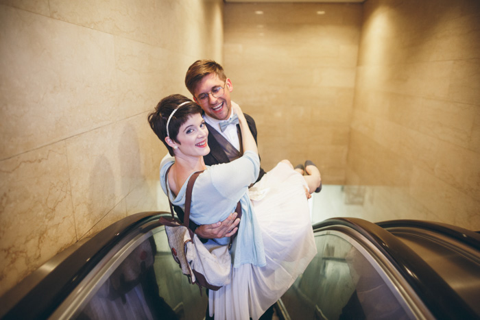 groom carrying bride on escalator