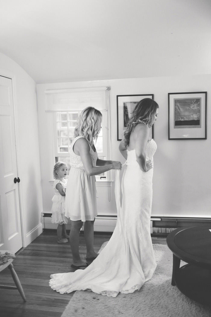 bride being zipped into dress