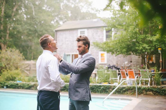 groom helping groomsman with tie