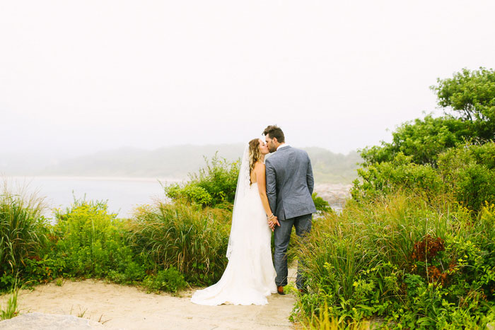 bride and groom kissing by the sea