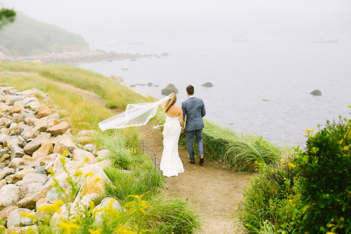 bride and groom walking towards the sea