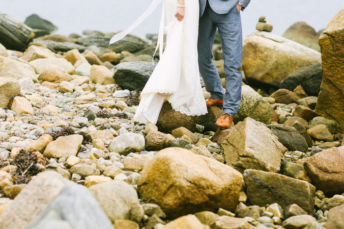bride and groom standing on rocks
