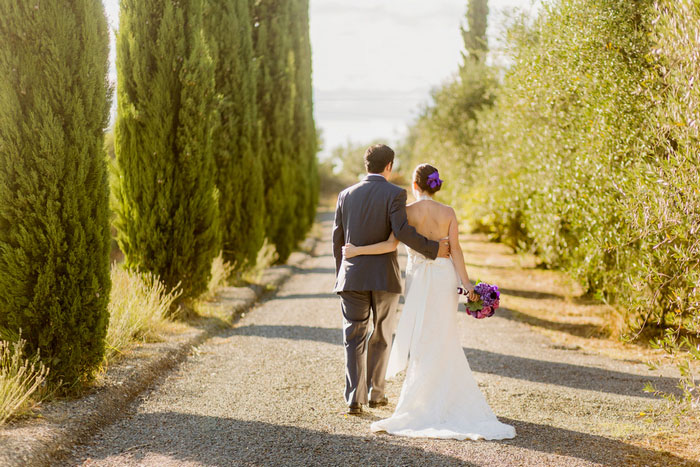 bride and groom walking down Tuscan Villa driveway