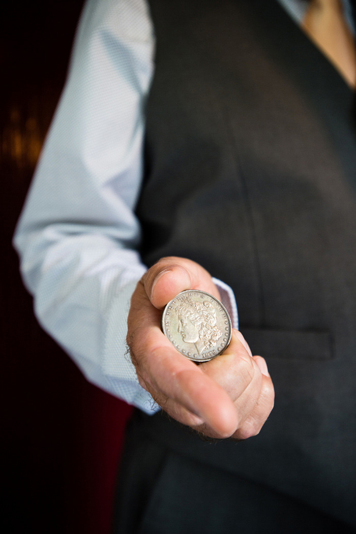 man holding large coin