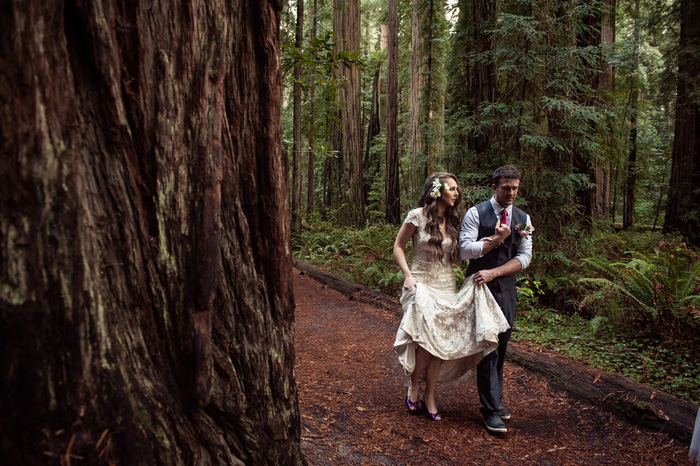 bride and groom walking in the woods