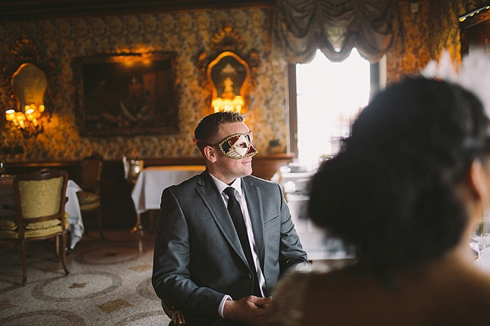 groom wearing masquerade mask