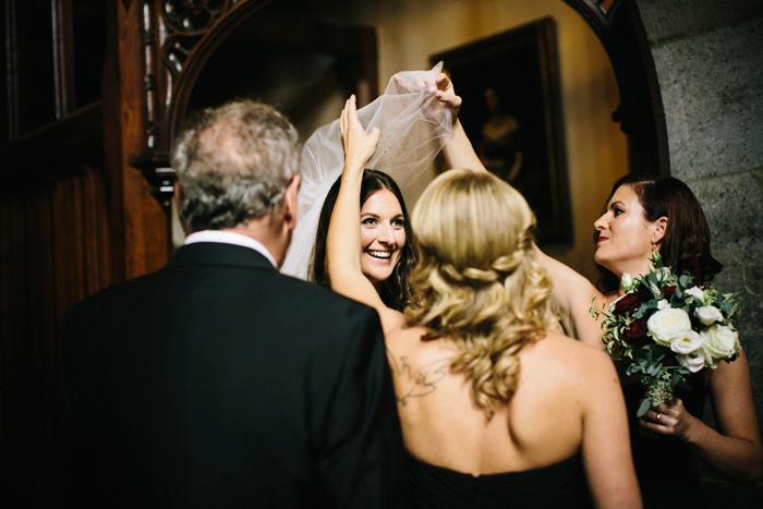 bridesmaids pulling bride's veil over her head