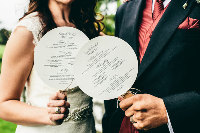 bride and groom holding wedding programs