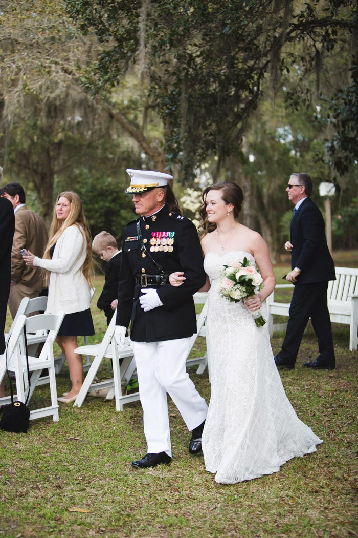 bride walking down the aisle with father in naval uniform