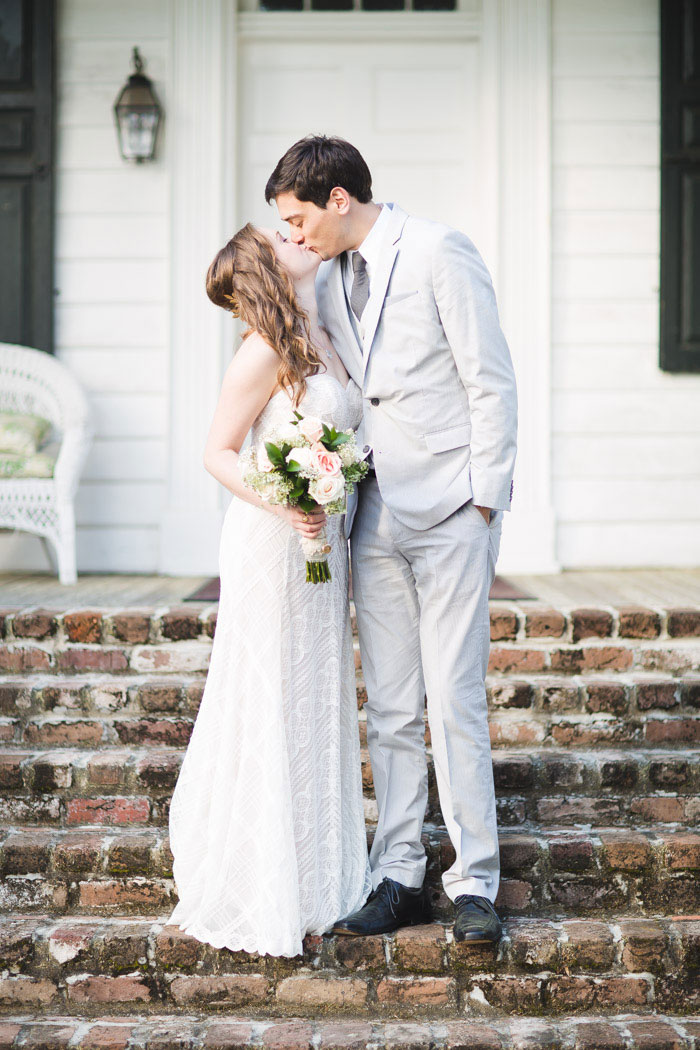 bride and groom kissing in front of porch