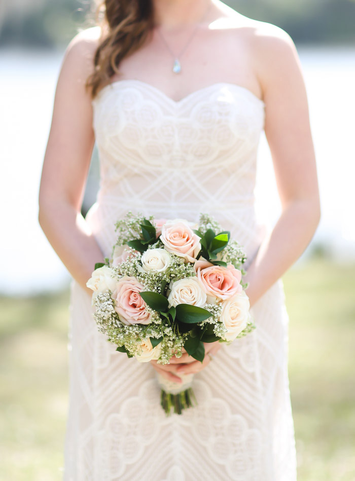 bride holding pink and white rose wedding bouquet