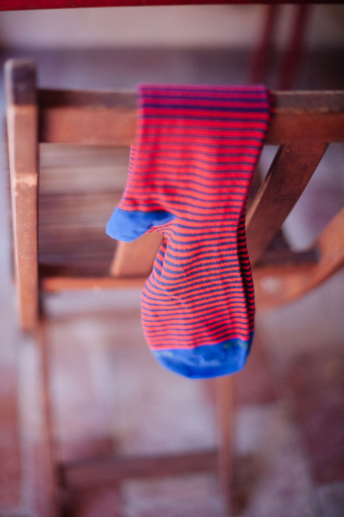 groom's red and blue striped socks hanging over chair