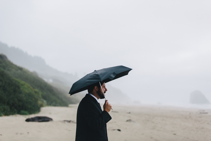 groom waiting on the beach under umbrella