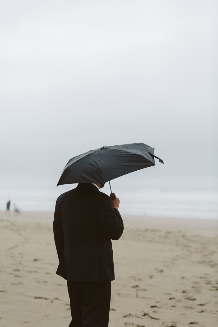groom on beach under black umbrella