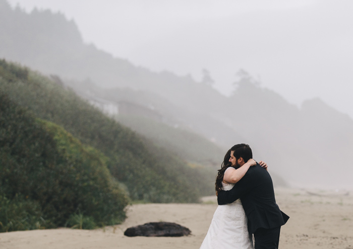 bride and groom hugging on the beach