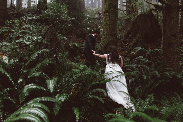 bride and groom hiking through oregon forest