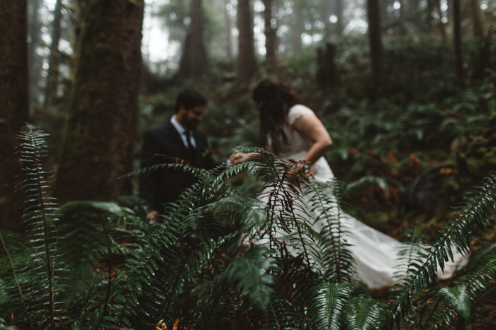 groom helping bride over log in forest