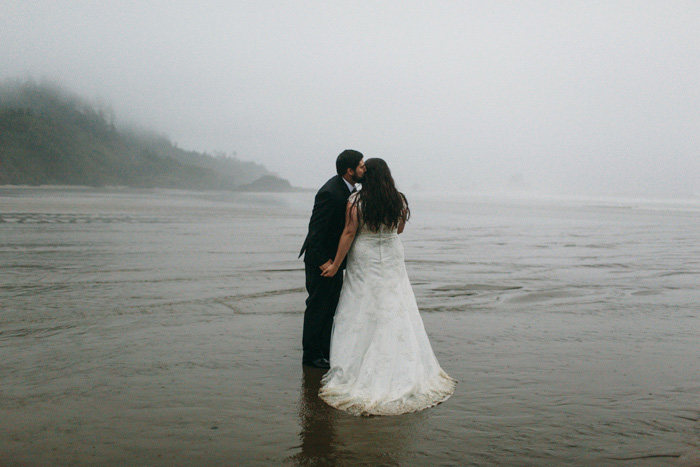 bride and groom kissing on foggy Oregon beach