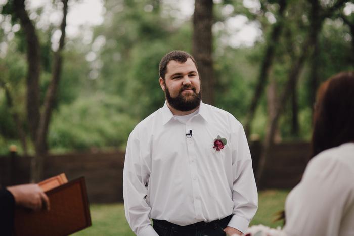 groom watching his bride walk down the aisle