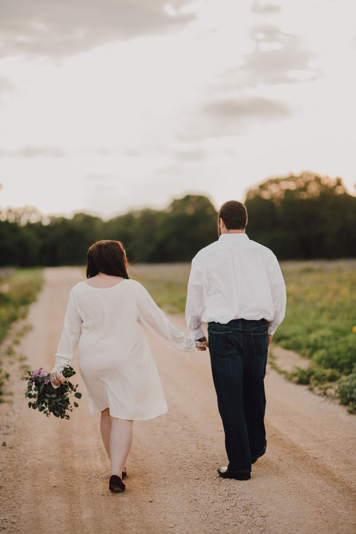 bride and groom walking down dirt road