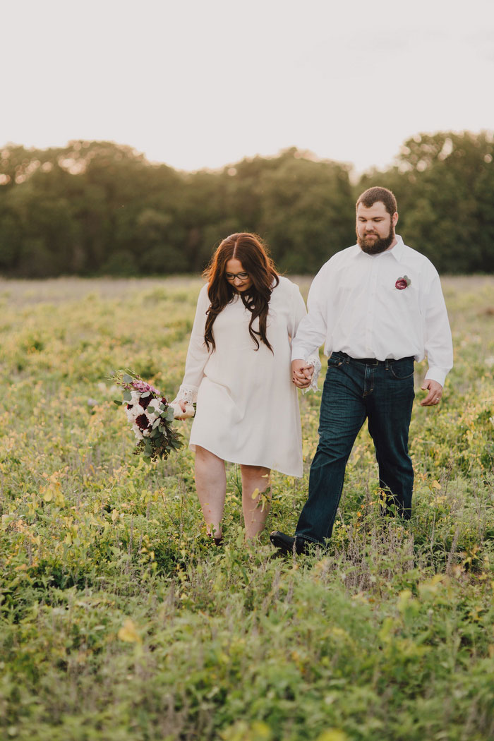 bride and groom walking across field at sunset