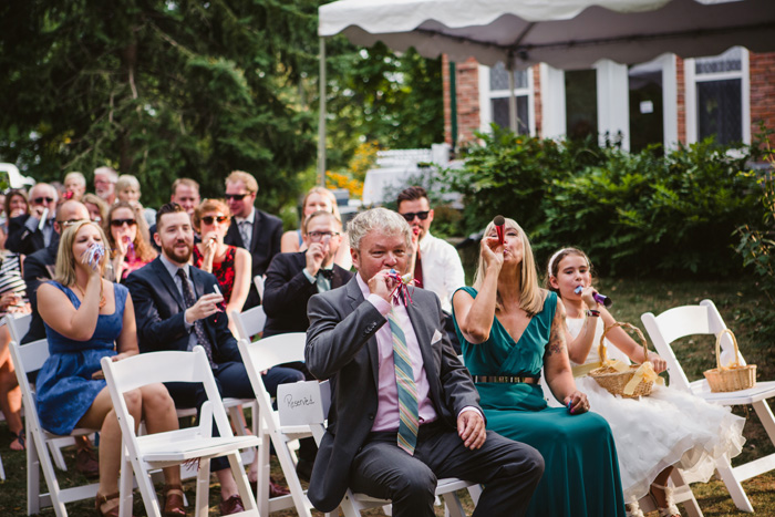 guests with party blowers at ceremony