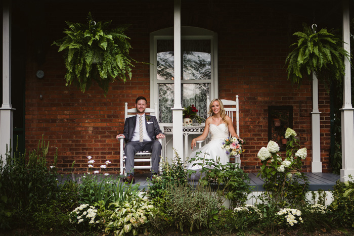 bride and groom sitting on inn porch
