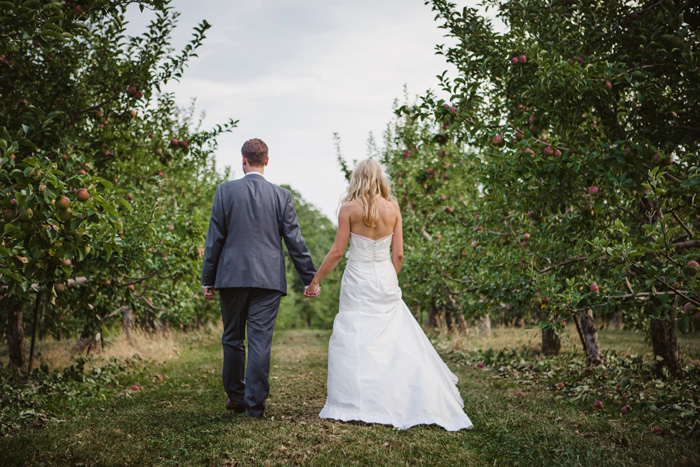 bride and groom walking though apple orchard