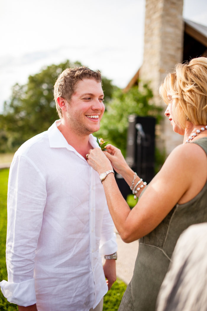 groom having boutonniere pinned on
