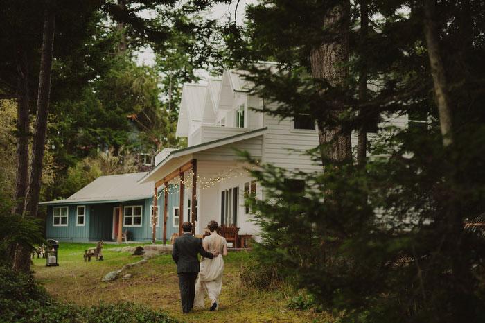 bride and groom walking toward house