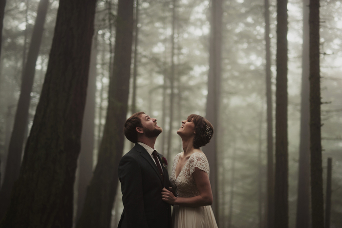 bride and groom looking up at the trees